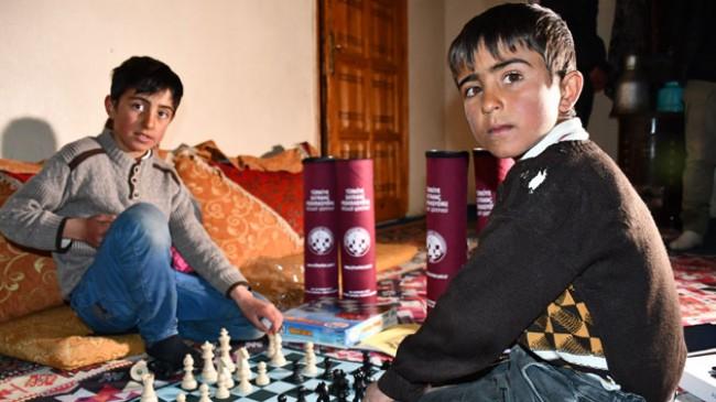 Pet şişe kapakları ile satranç oynayan çocuklara satranç takımı